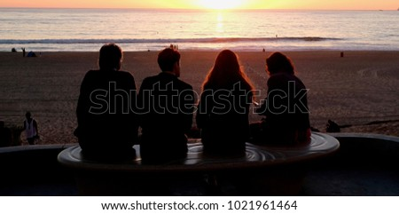 A family spending some time at the beach during a sunset