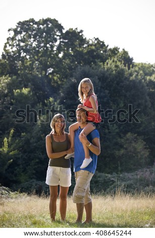 A family standing in a park, father carrying his daughter on his shoulders - stock photo