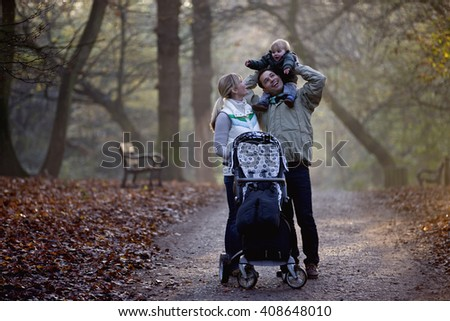 A family standing in the park, father carrying his son on his shoulders - stock photo