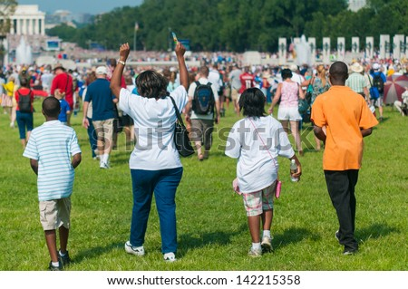A family walking with purpose and pride at a rally on the National Mall in Washington, DC. - stock photo
