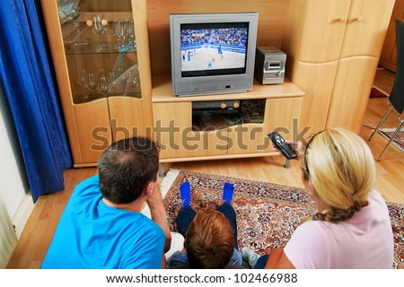 a family watching tv with tv - stock photo