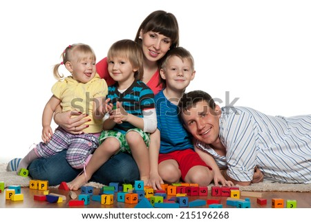 A family with children are playing on the floor - stock photo
