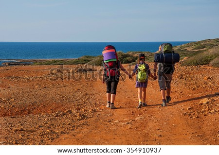 A family with large backpacks are on the sandy road to the sea