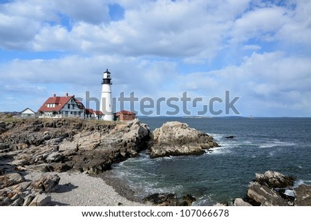 A famous New England Lighthouse along the rocky shore. Portland headlight. - stock photo