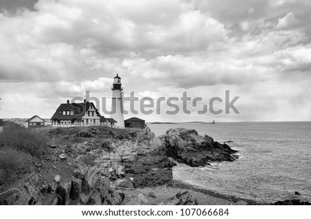 A famous New England Lighthouse along the rocky shore. Shown here in black and white.