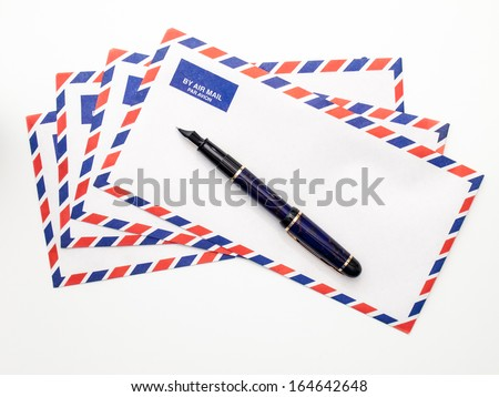 A fan of airmail envelopes and a fountain pen on a white background