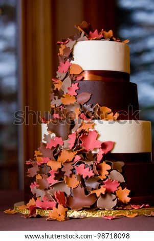 A Fancy fall themed wedding cake with sugar leaves falling down the side - stock photo