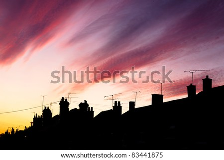A fantastic sunset lights up the clouds above an urban street in Surrey, UK. - stock photo