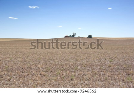 a farm house at the top of a dry field in the drought