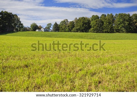 A farm house perched on a hill above a freshly mowed field. - stock photo