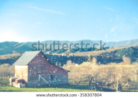 a farm in countryside  view from  a car with rain splash in the mirror. - stock photo