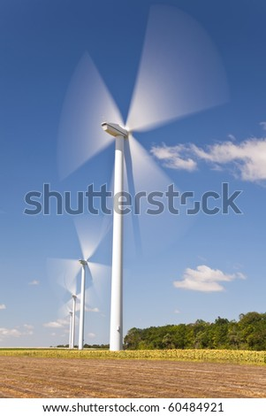 A farm of wind turbines or windmills providing alternative sustainable green energy, situated in a field of sunflowers - stock photo
