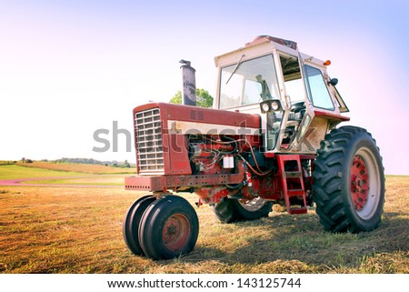 A farm tractor in a freshly mowed field - stock photo