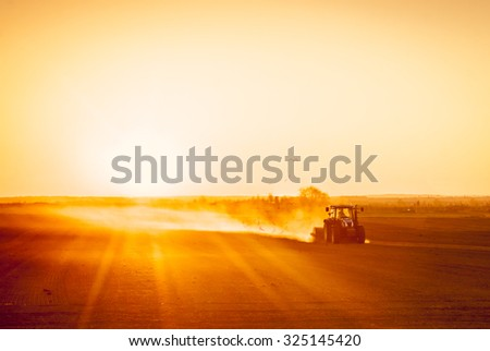A farmer in a tractor prepares his field as the sun begins to set. The tractor is backlit by the setting sun. The sun is setting behind a low row of hills in the far distance. - stock photo
