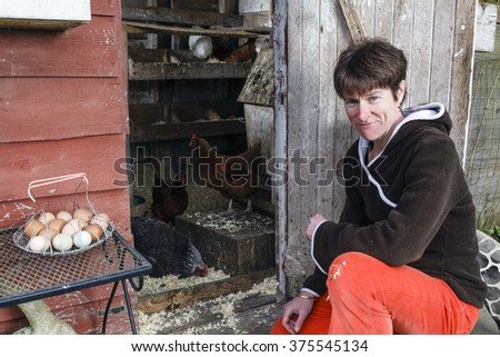 A farmer outside her chicken enclosure with eggs and chickens.