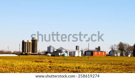 A farmers agricultural silos and equipment among the field where he works outside during the winter - stock photo