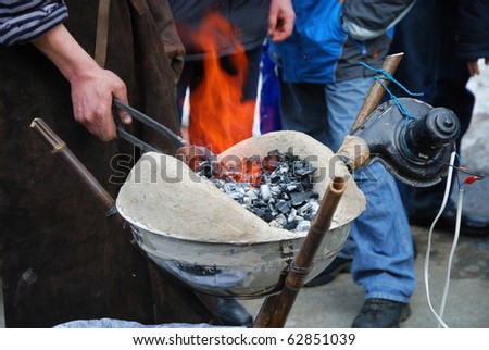 A farrier is working with portable forging furnace. In the photo we can see the human hand holding tongs with handicraft.