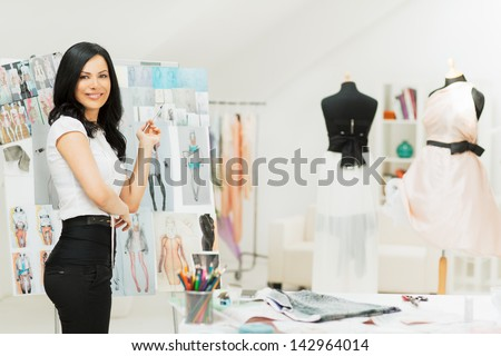 A fashion designer sorting out her new sketches. - stock photo