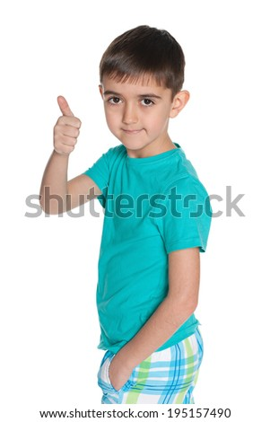 A fashion little boy holds his thumb up on the white background