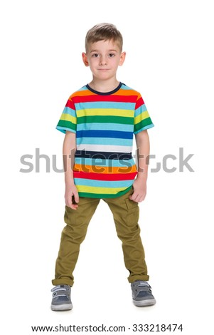 A fashion little boy stands against the white background - stock photo