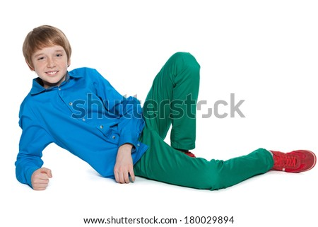 A fashion preteen boy is lying on the white background