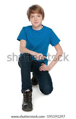 A fashion preteen boy is sitting on the white background