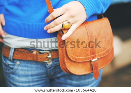 A fashion shoot of a woman in blue jeans and a blue sweater, wearing a ginger ring, a ginger leather belt and holding a ginger leather bag in her hand - stock photo