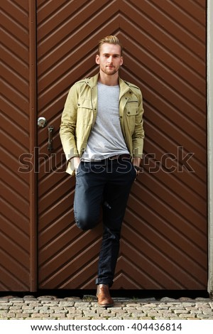 A fashionable man in his 20s wearing a yellow jacket and dark pants, leaning against a big wooden door outside in a city. Feeling laid back and relaxed. - stock photo