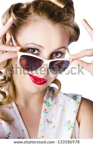 A fashionable woman holding her sunglasses on her nose and looking over them - stock photo
