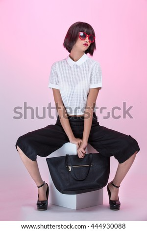 A fashionable young girl wearing sunglasses, holding a black purse, sitting - stock photo