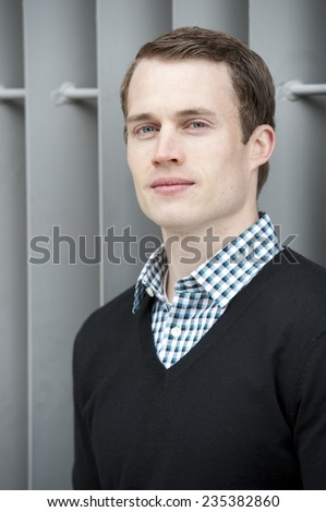 A fashionable young good looking man posing on a steel background on a sunny day. - stock photo