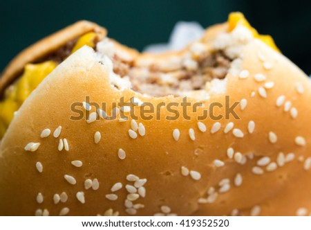 A fast food cheeseburger with a bite taken out of it /  one bite taken out of it / Bitten hamburger. - stock photo