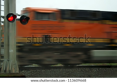 A fast moving freight train speeds past an intersection - stock photo