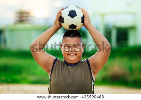 A fat boy playing soccer football for exercise under the sunlight.
