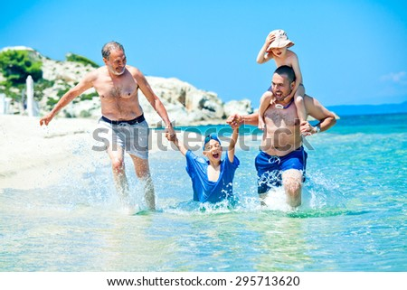 A father and a grandfather on vacation are pulling a young boy through the sea water, other on the shoulders, having fun running under the summer sun.