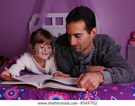 A father and daughter spend time together reading a  book - stock photo