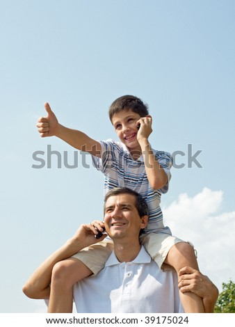 a father and his son are looking forward and speaking over mobiles - stock photo