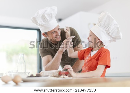 a father and his son preparing a cake in the kitchen - stock photo