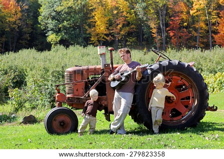 A Father and his two young boy children are relaxing on a farm, playing guitar by an old tractor in the autumn woods, on a fall day. - stock photo