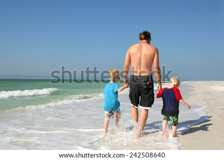 A father and his two young children, both sons, are holding hands as they walk along a white sand beach, through the ocean while on summer vacation. - stock photo
