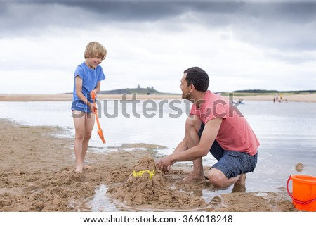A father and son are building sand castles on the beach - stock photo