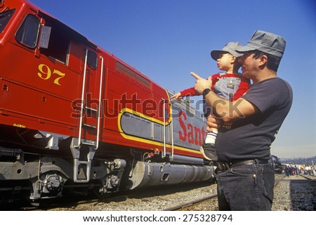 A father and son in engineer caps look at a historic Santa Fe diesel train in Los Angeles, CA - stock photo