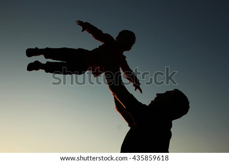 a father and son silhouette on sunset - stock photo