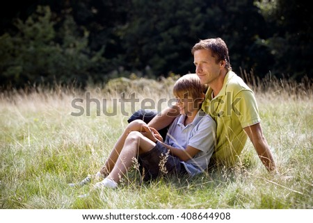 A father and son sitting on the grass - stock photo