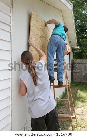 A father and son working together to board up their house for a hurricane. - stock photo