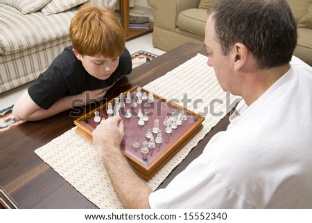 A father and ten year old son playing chess indoors - stock photo