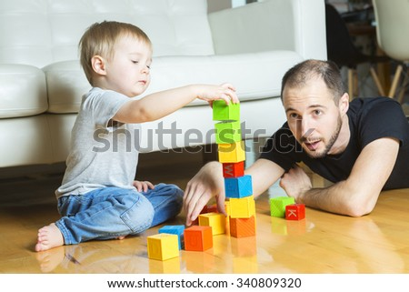 A father play block with his son at home - stock photo
