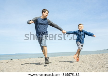 A father play with is son on the side of the beach
