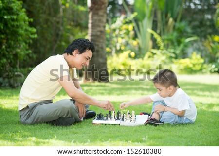 A father playing chess with his little son outside - stock photo