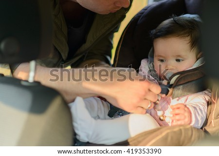 A father putting his baby daughter into her car seat in the car